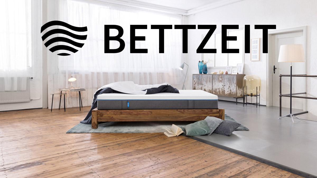Bett in einem Zimmer mit Bettzeit Logo