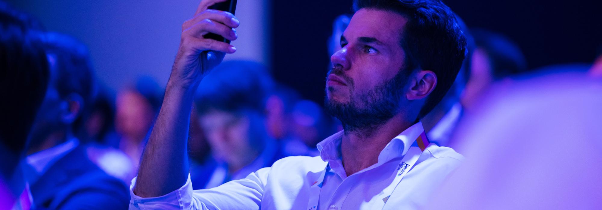 Helge Ruff mit Handy auf der Konferenz