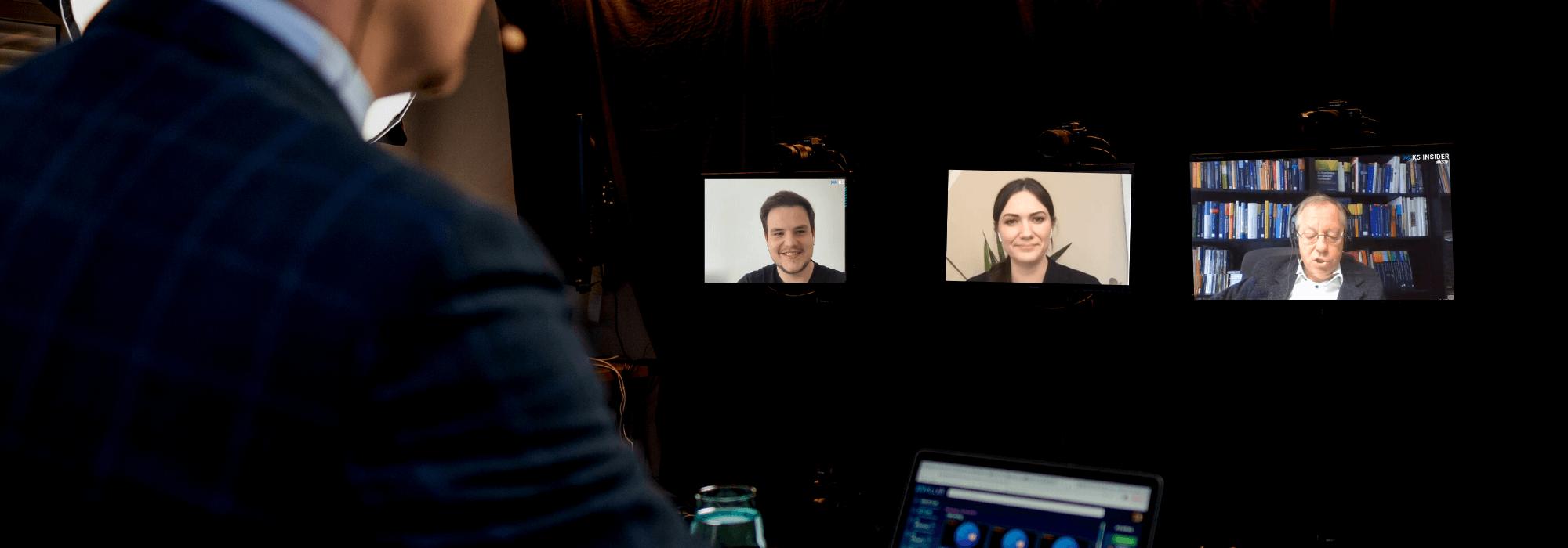 Blick über die Schulter von Sven Rittau auf die Bildschirme der Studiogäste
