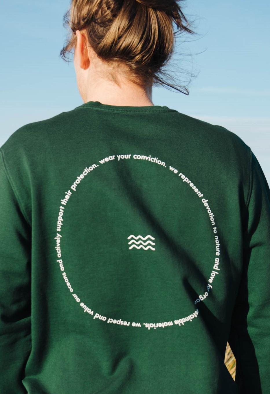 Auf dem Foto ist eine Frau von hinten zu sehen. Sie trägt einen dunkelgrünen Sweatshirt der Marke Salzwasser. Auf dem Sweatshirt ist eine weiße Schrift in Form eines Kreises aufgetragen.